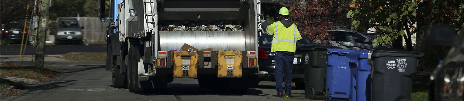 worker walking next to large truck collecting recyclables along a street