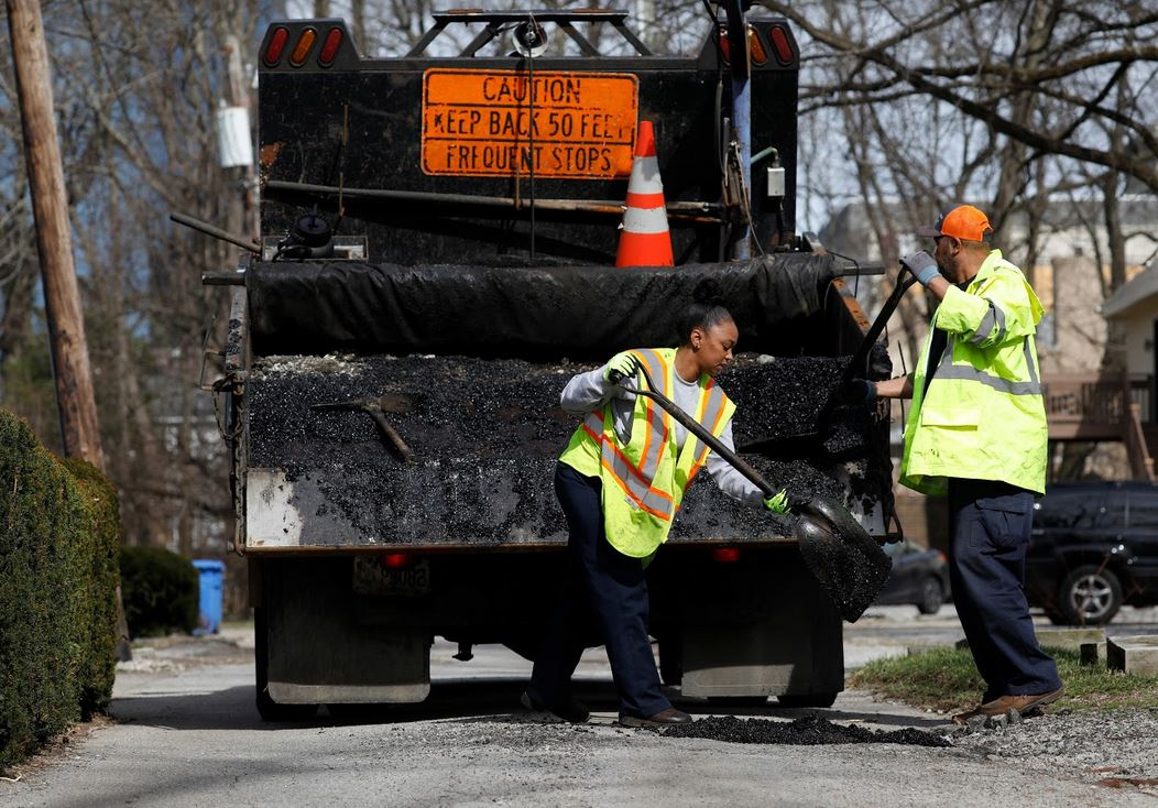 two employees in high-vis vests patching a pothole in the road