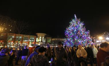 nighttime photo of large Christmas tree in downtown Lexington with a crowd around it