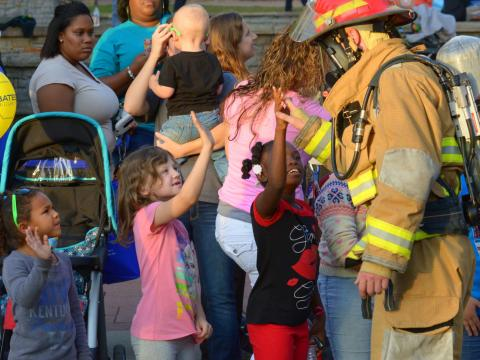Firefighter giving a high-five to a group of children.