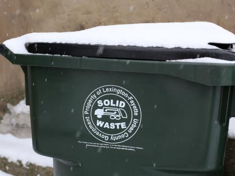 Green waste container with snow on top.