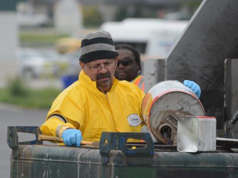 Image of city employee disposing of oil waste