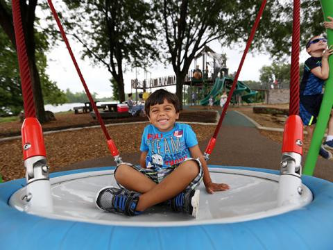 Child plays on swing at Jacobson Park's new playground