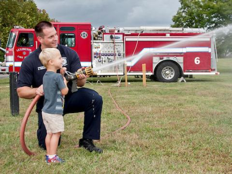Firefighter with young child at festival.