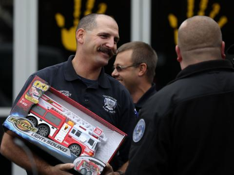 firefighter holding toy truck