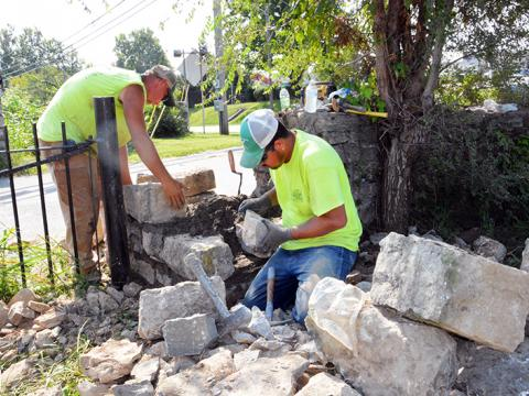 Crew of stonemasons rebuilding stone fence