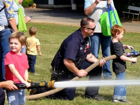 Image of firefighters and kids with fire hoses