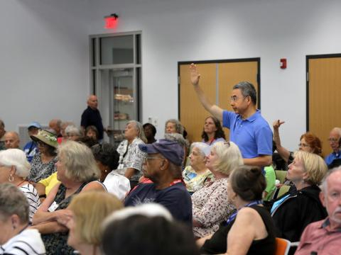 Image of person asking a question at a Senior Center workshop