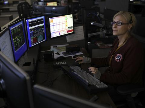 female 911 calltaker sitting in darkened room in front of computer screens