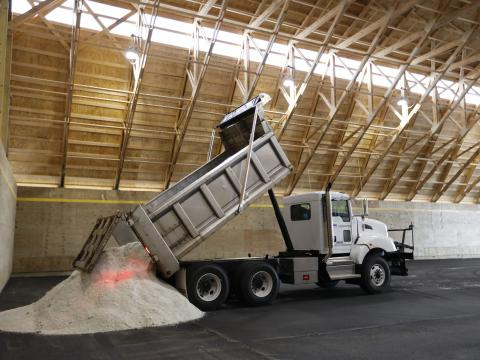 truck dumping a load of salt into a new barn