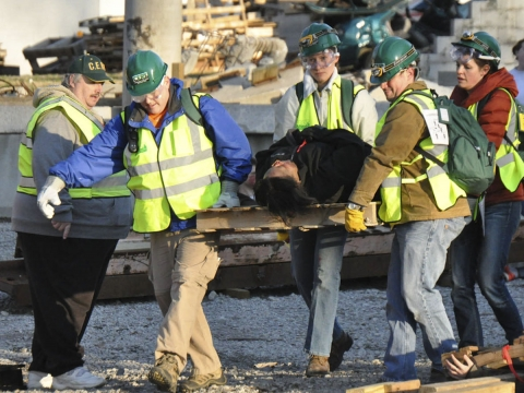 four people wearing hard hats and bright vests carry a person laying on a board