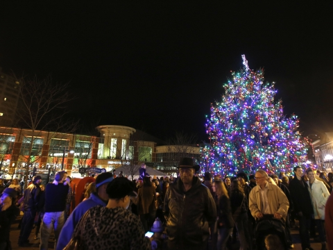 large Christmas tree in a downtown public square with many people around it